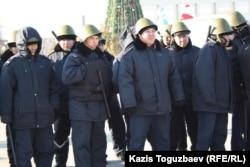 Полицейские в железных касках и бронежилетах, вооруженные резиновыми дубинками на центральной площади города. Актау, 18 декабря 2011 года.