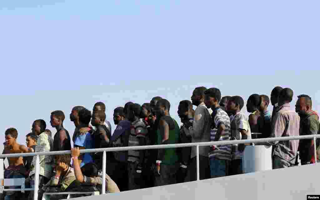 Нелегальные мигранты сходят с британского судна охраны в итальянском городе Поццалло, на Сицилии