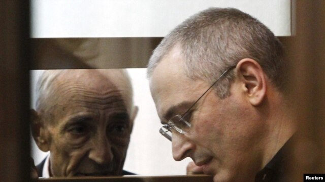 Mikhail Khodorkovsky speaks to a lawyer as he stands in the defendants' box during a court session in Moscow on May 24, 2011.