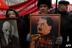 Russian communist supporters carry portraits of Soviet Union founder Vladimir Lenin and Soviet leader Joseph Stalin as they take part in a demonstration marking the 99th anniversary of Russia's Bolshevik Revolution in Moscow on November 7.