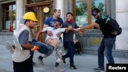 Участники акции протеста несут раненого во время акции на площади Таксим в Стамбуле, 11 июня 2013