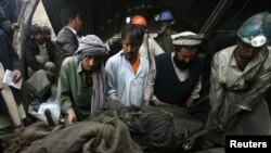 Pakistan -- Rescue workers retrieve the body of one of the miners who was killed in a explosion sparked by methane gas inside a coal mine in Surran range, 20Mar2011