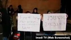 Молодые люди, вооруженные транспарантами и мегафонами, требуют от Элене Хоштария сложить депутатские полномочия
