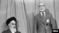 Ayatollah Rohollah Khomeini introduces liberal Mehdi Bazargan as interim prime minister during the Islamic Revolution, Feb1979. Notable that Bazargan is wearing a tie, which was later banned as a Western symbol.