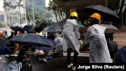 Дэманстранты ў масках трымаюць парасоны падчас пратэстаў у цэнтральным Ганконгу