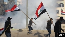 U.S. forces (unseen) fire teargas canisters at supporters and members of the Hashed al-Shaabi paramilitary force during a demonstration outside the US embassy in the Iraqi capital Baghdad on January 1, 2020.