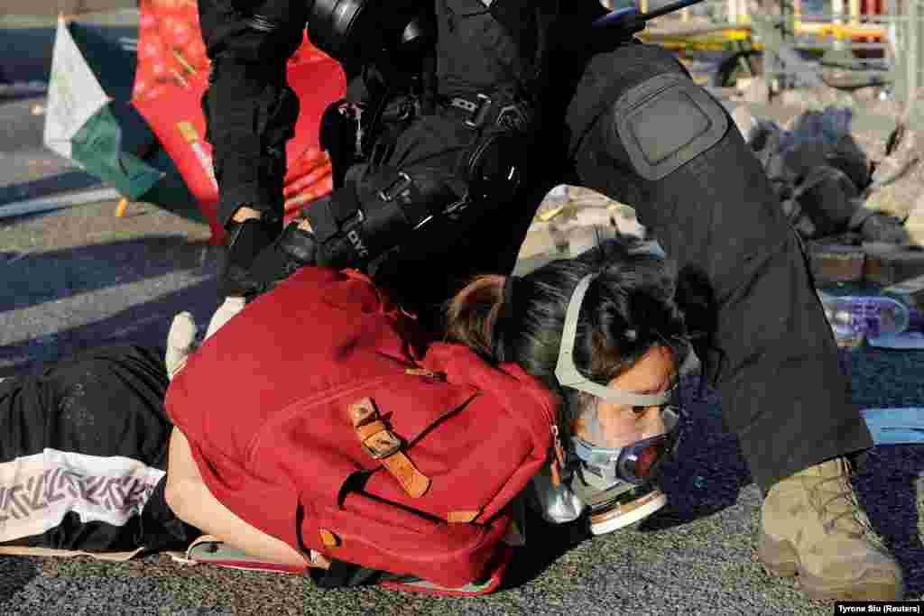 Полициянын атайын кызматкери Кытай Эл Республикасынын 70 жылдыгында бийликке каршы митингге чыккан жаранды кармап кетип баратат. Гонконг. 1-октябрь, 2019-жыл.