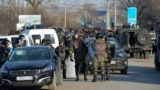 Kazakhstan Violence - Kazakhstan's riot police attend a blocked road after the conflict in Masanchi, near the border with Kazakhstan, Saturday, Feb. 8, 2020, a large population of Dungan, who are Muslims of Chinese ancestry. Kazakhstan's interior minister