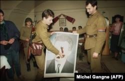 Румынские солдаты, перешедшие на сторону революции, оскверняют портрет диктатора Чаушеску. Декабрь 1989 года