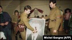 Солдаты режут портрет Чаушеску после его свержения, декабрь 1989
