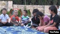"""""""Қазақстандық жиһадшылар"""" туралы видеодағы жасы 8-9 жасар Дінмұхаммед (қызыл шеңберде) ретінде танылған бала. (Скриншот YouTube видеосынан алынды)"""