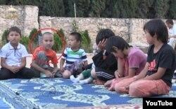 Дети «джихадистов из Казахстана в Сирии», сидящие во дворе большой виллы и читающие Коран. Кадр с сайта Youtube. Время, авторство и место съемки неизвестно.