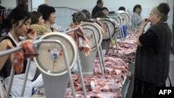 Продавцы и покупатель в мясном павильоне рынка.