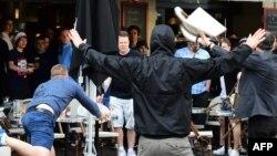 یکی از هواداران افراطی روسیه صندلیهای کافهای را به سوی هواداران انگلستان پرتاب میکند