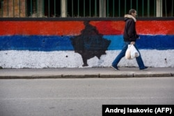 A pedestrian walks past a wall painted in the colors of the Serbian national flag with a map of Kosovo in the middle, in Belgrade on February 12, 2018.