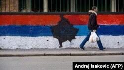 Пішохід біля стіни, розфарбованої в кольори сербського національного прапора з картою Косово посередині, Белград, 12 лютого 2018 року