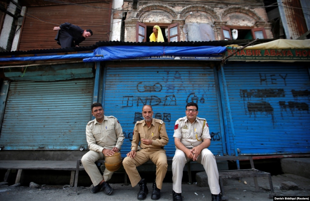 Индийская полиция перед закрытыми магазинами в Сринагаре. 6 августа 2019 года. Пакистан приостановил торговлю с Индией в знак протеста против действий Нью-Дели. Уровень дипломатических отношений между двумя странами понижен.