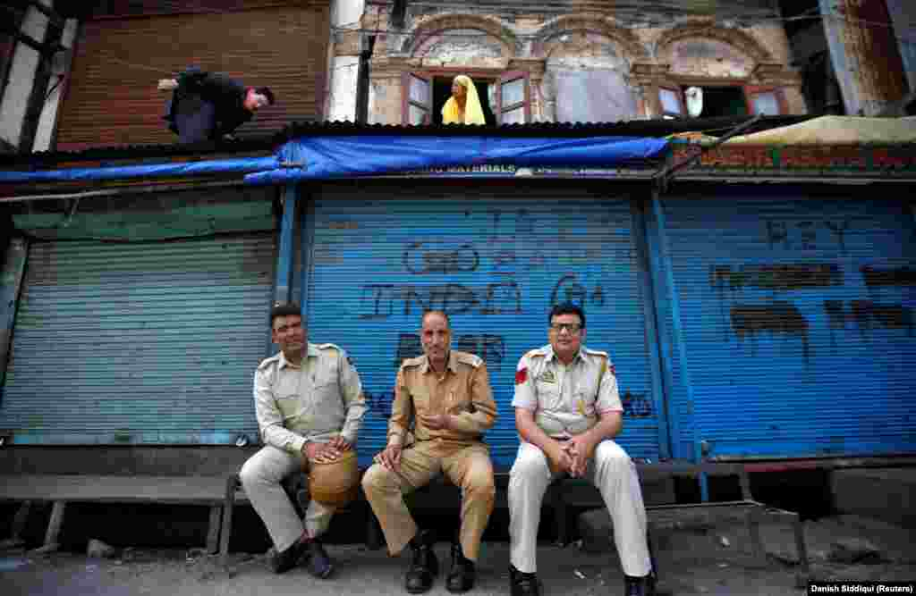 Indian police in front of shuttered shops in Srinigar on August 6. Pakistan has downgraded diplomatic links with India and suspended trade in protest of New Delhi's move.