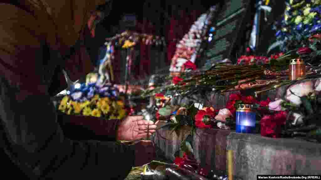 Девушка зажигает свечу перед мемориальной доской на улице Институтской.