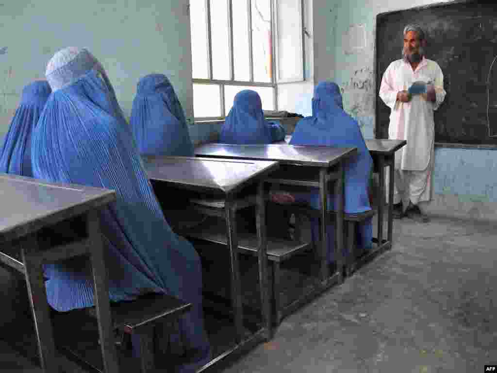 Schoolgirls in burqas listen to their male teacher in the outskirts of Afghanistan's Herat Province.