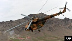 An Afghan National Army (ANA) helicopter flies over a military base during an exercise mission on the outskirts of Kabul on March 16.
