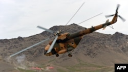 FILE: A Russian made helicopter flies over a military base as commando forces demonstrate their skills during an exercise mission at Commando Unit Base on outskirts of Kabul in March 2013.