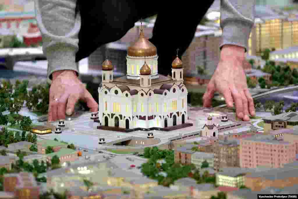 Radnik prilagođava maleni prikaz masivne katedrale Krista Spasitelja 29. listopada.