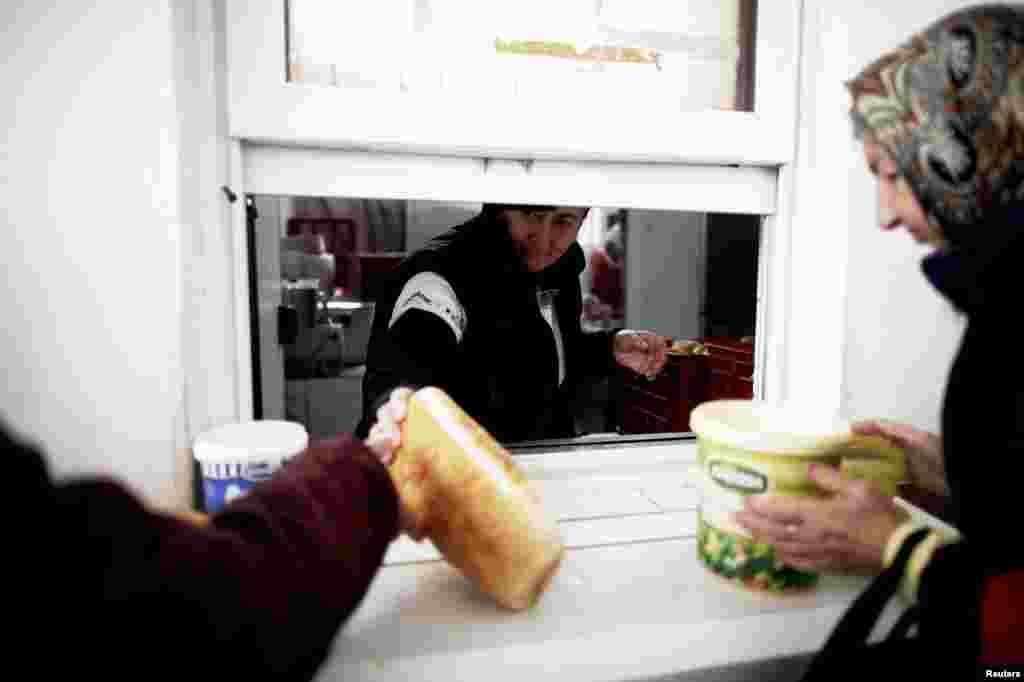 People receive food at one of Mostar's two soup kitchens -- one of the services threatened by the city's failure to approve the 2013 budget.