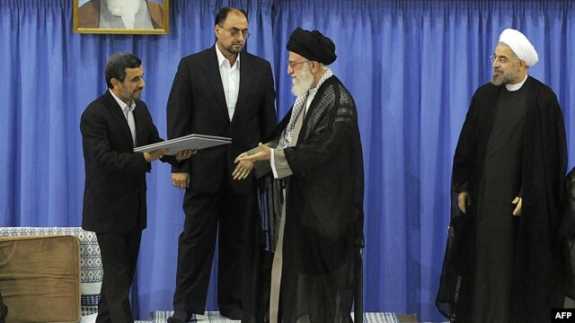 Exiting President Mahmud Ahmadinejad (left) handed the official endorsement document to Supreme Leader Ayatollah Ali Khamenei (second from right) on August 3 as President-elect Hassan Rowhani (right)) looked on.