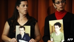 The mothers of Americans Josh Fattal and Shane Bauer and Laura Fattal (left to right) hold their sons' photos at a September press conference in New York.