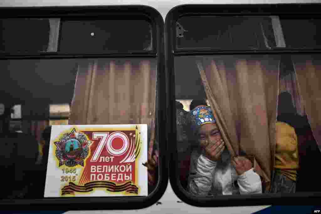 Young actresses laugh as they look out a window while they prepare to perform in the city of Baikonur to celebrate Maslenitsa (Shrovetide), a farewell ceremony for winter. Shrovetide precedes the beginning of Lent, with each day of the week holding its own meaning. Shrove Sunday, also known as the Sunday of Forgiveness, is a day for asking forgiveness for the harm caused to other people, intentionally or unintentionally. (AFP/Kirill Kudryavtsev)