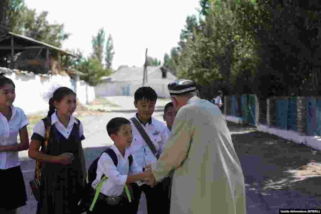 Сексената ауылындағы оқушылар ақсақалға сәлем беріп тұр.