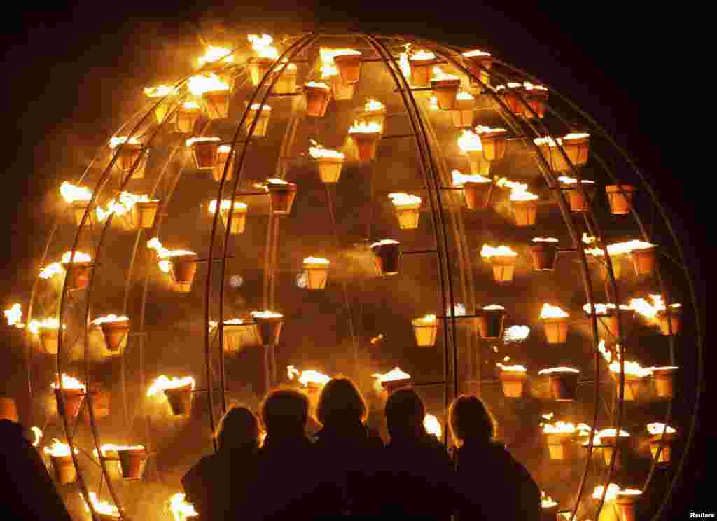 Women look at a metal structure filled with flaming flower pots during an elemental Fire Garden display at Stonehenge, which is part of the London 2012 Olympics festival. (REUTERS/Kieran Doherty)
