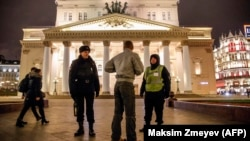 A police officer and a security staff member speak with a passerby outside the Bolshoi Theatre in Moscow after a bomb threat in early November.