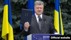 Ukrainian President Petro Poroshenko displays the fully ratified Association Agreement between Ukraine and the European Union in Kyiv on July 13.