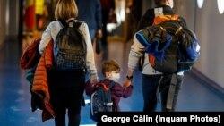 O familie purtând măști chirurgicale, pe aeroportul Otopeni din Bucuresti