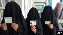 Burqa-clad women show ID cards as they wait to cast their votes in Kandahar. Is their willingness to participate a sign of Taliban weakness?