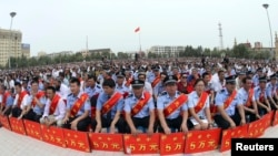 "Police wearing sashes hold placards during a ceremony to award those who the authorities say participated in ""the crackdown of violence and terrorists activities"" in China's Xinjiang Uyghur Autonomous Region."