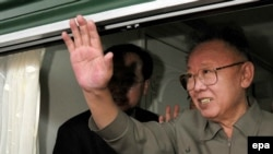 Kim Jong Il waves from a window during his visit to China in May.