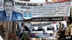 Banners of Egypt's Muslim Brotherhood candidate, Muhammad Morsi (front) and his rival, former leader Hosni Mubarak's last prime minister, Ahmed Shafiq, decorate a street in Cairo.