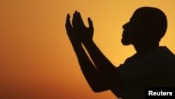 Мужчина поднимает руки, чтобы помолиться у моря на закате, после целого дня поста в священный месяц Рамадан в Бенгази, Ливия.