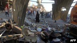 Люди на месте взрыва автомобиля в шиитском квартале Багдада.