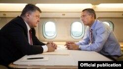 Президент України Петро Порошенко (ліворуч) та генеральний секретар НАТО Єнс Столтенберґ спілкуються у салоні літака по дорозі з Києва до Львова. 21 вересня 2015 року