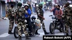 Jammu sebitinde howpsuzlyk işgärleri motosikletdäki adamlary soraga çekýär. 5-nji awgust, 2019 ý.