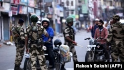 Indian security personnel question motorists during curfew-like restrictions in the city of Jammu on August 5.