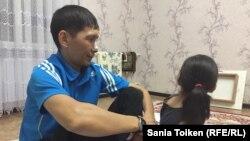 Мұнайшылар белсендісі Мақсат Досмағамбетов қызымен бірге үйінде отыр. Жаңаөзен қаласы, 30 қыркүйек 2017 жыл.