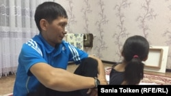 Maksat Dosmaghambetov (left) sits with his daughter at home in Zhanaozen on September 30, 2017.