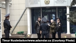 Активисты Асия Тулесова (в центре слева) и Бейбарыс Толымбеков (третий слева) у здания суда перед началом разбирательства, Алматы, 21 апреля 2019 года.