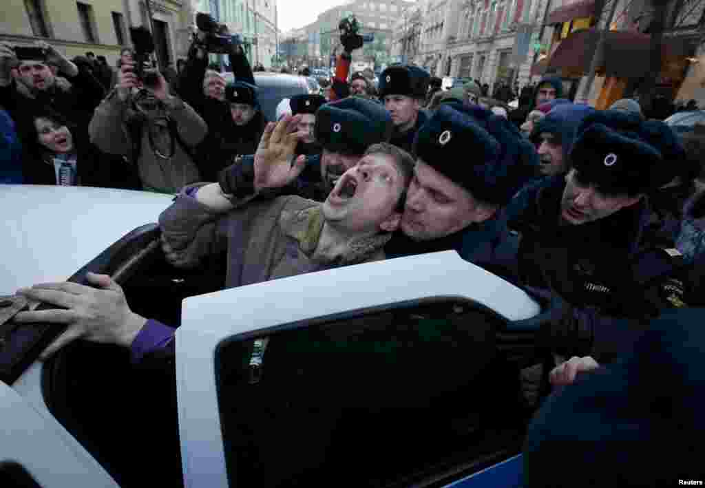 Police officers detain a demonstrator who was taking part in a protest by foreign-currency mortgage-holders near Central Bank headquarters in Moscow on February 8. (Reuters/Sergei Karpukhin)