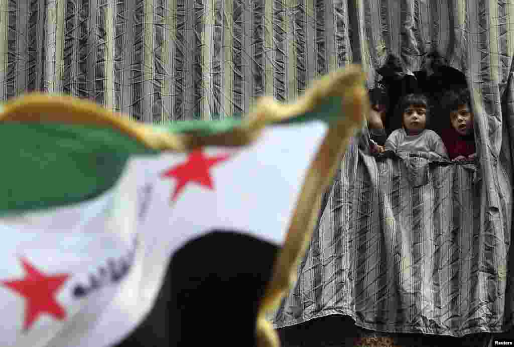 A woman and children stand on a balcony as they watch people protesting against Syria's President Bashar al-Assad in Aleppo. (Reuters/Muzaffar Salman)